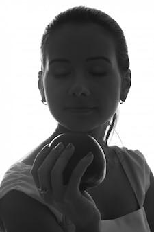 Belle jeune fille vous remettant une pomme rouge saine. isolé