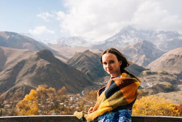 La belle jeune fille voyage, apprécie le paysage de montagne, sourit