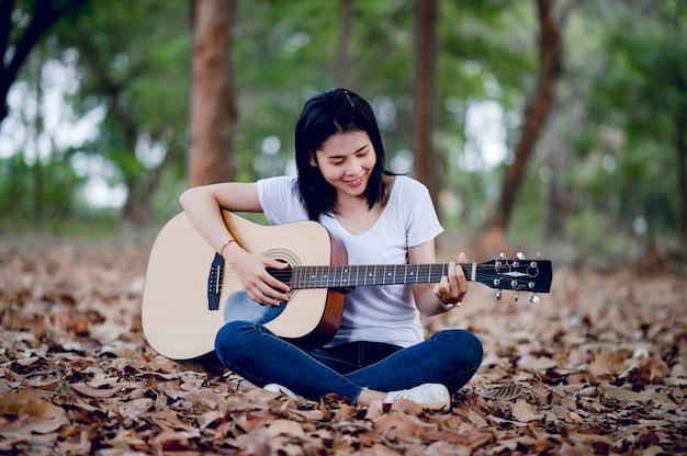 Belle jeune guitariste jouant de la guitare avec bonheur dans le jardin, forêt naturelle, concept musical