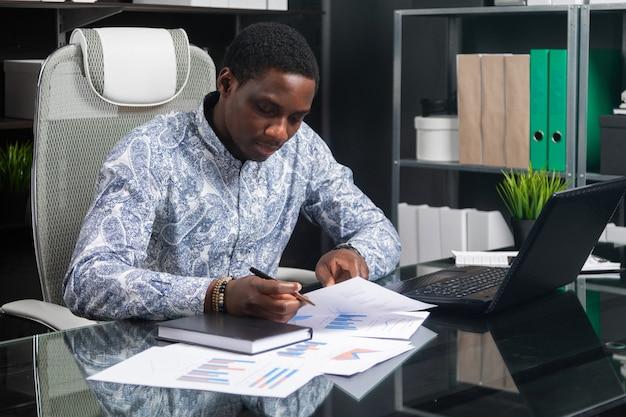 Belle jeune homme d'affaires afro-américain travaillant avec des documents et un ordinateur portable au bureau