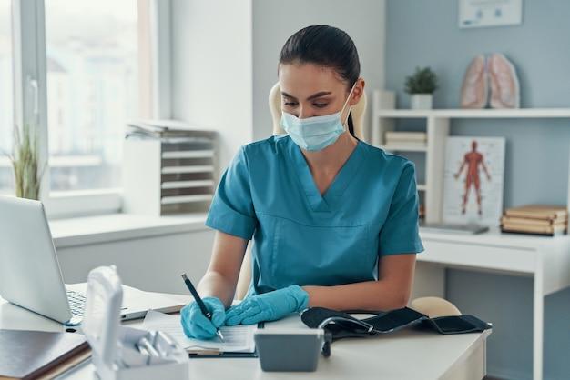 Belle jeune infirmière portant un masque de protection écrivant quelque chose alors qu'elle était assise dans son bureau
