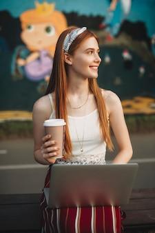 Belle jeune influenceuse aux cheveux roux et aux taches de rousseur assis sur un banc avec un ordinateur portable sur ses jambes et une tasse de café dans une main en détournant les yeux en souriant.