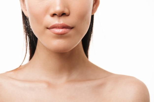 Belle jeune jolie femme asiatique avec une peau saine posant isolée