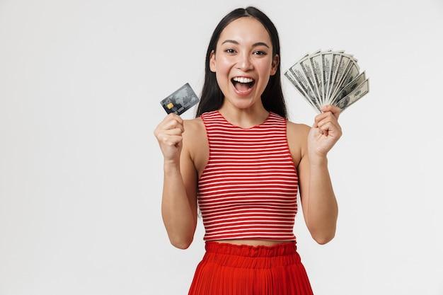 Belle jeune jolie femme excitée asiatique posant isolée sur un mur blanc tenant une carte de crédit et de l'argent.
