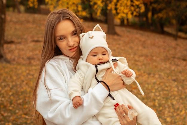 Belle jeune maman avec bébé fille à l'automne