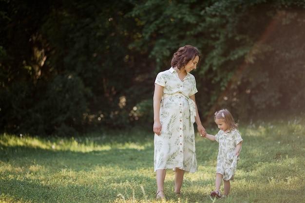 Une belle jeune maman enceinte et sa petite fille cueillent des fleurs dans un champ. maternité. une famille. été.