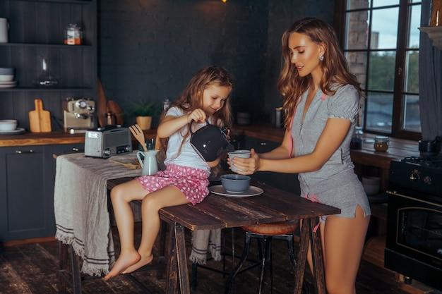 Belle jeune maman joue et s'amuse avec sa petite fille mignonne dans un intérieur de cuisine sombre à la maison