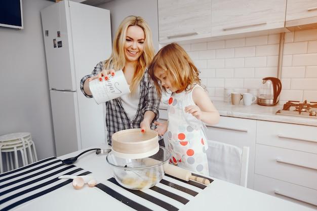 Une belle jeune maman avec sa petite fille cuisine dans la cuisine à la maison