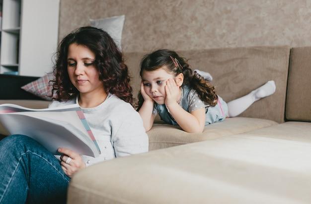 Une belle jeune maman et sa petite fille dessinent avec des crayons dans un album. mère et fille s'amusent à la maison.