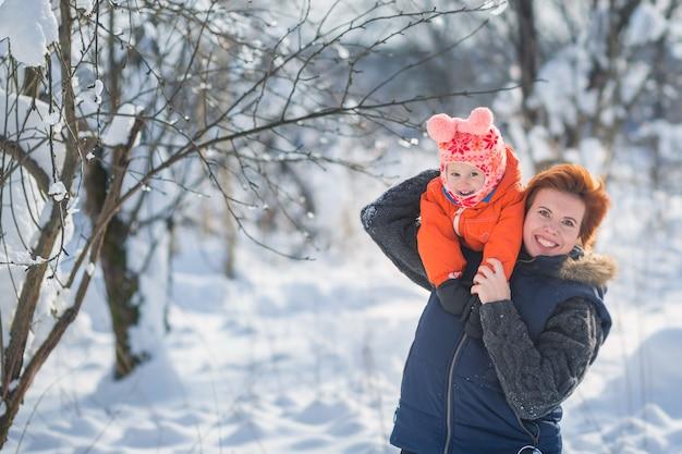 Belle jeune maman et sa petite fille mignonne s'amusent en plein air en hiver.