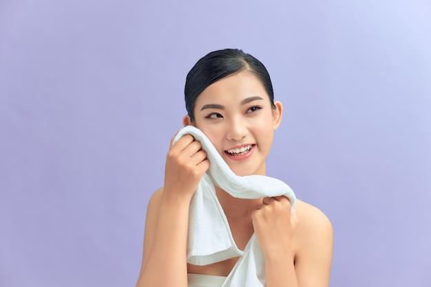 Belle jeune mannequin asiatique souriante et souriante essuyant la peau du visage avec une serviette douce, enlevant le maquillage