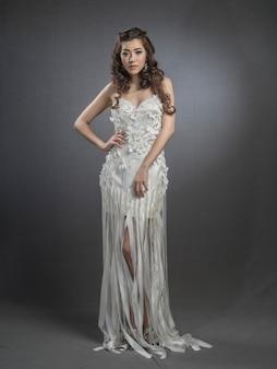 Belle jeune mannequin brune posant en robe de mariée
