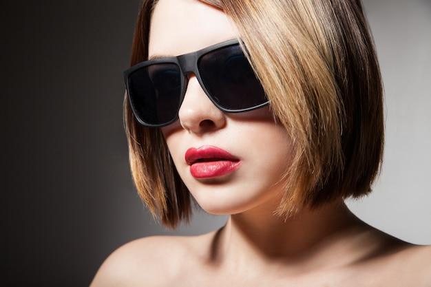 Belle jeune mannequin avec de grosses lunettes
