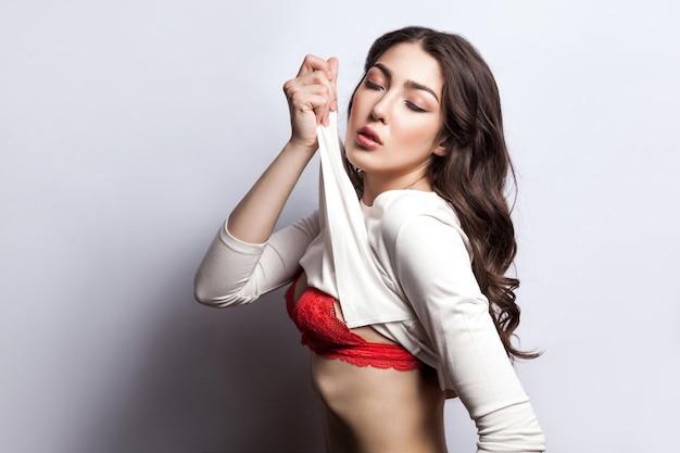 Belle jeune mannequin. jeune mannequin sensuelle, yeux fermés, se déshabillant et posant devant la caméra. isolé sur fond gris, tourné en studio