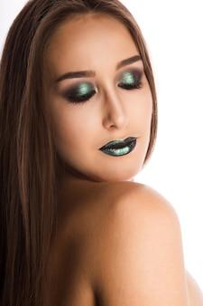 Belle jeune mannequin avec une peau parfaite et un maquillage vert métallique créatif. closeup portrait en studio sur fond blanc