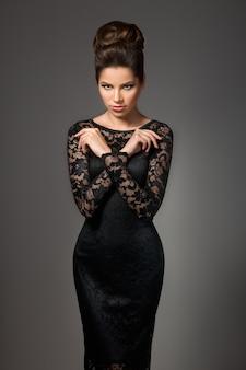 Belle jeune mannequin en robe noire avec maquillage de soirée et coiffure posant sur fond gris