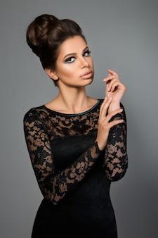 Belle jeune mannequin en robe noire avec maquillage de soirée et coiffure posant sur gris