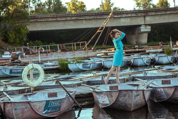 Belle jeune mannequin en robe turquoise et maquillage et coiffure de mode pose sur la jetée, pose et regarde la caméra.