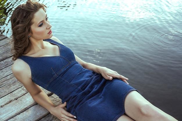 Belle jeune mannequin avec des taches de rousseur sur son visage et une robe bleu denim et un maquillage et une coiffure de mode est allongée sur la jetée, posant et regardant au loin.