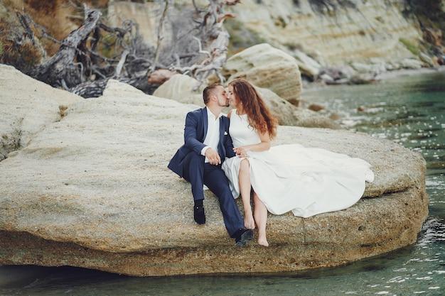 Belle jeune mariée aux cheveux longs en robe blanche avec son jeune mari près de la rivière