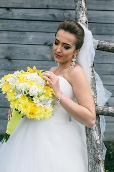 Belle jeune mariée avec bouquet est debout à l'échelle