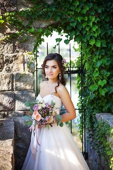 Belle jeune mariée avec un bouquet de fleurs de mariage. robe de vacances