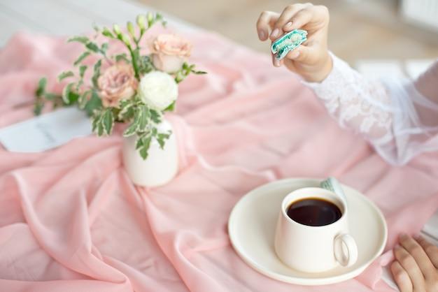 Belle jeune mariée caucasienne appréciant le petit-déjeuner du macaron français et du café sur une table en bois avec une nappe rose en mousseline de soie et un vase de fleurs