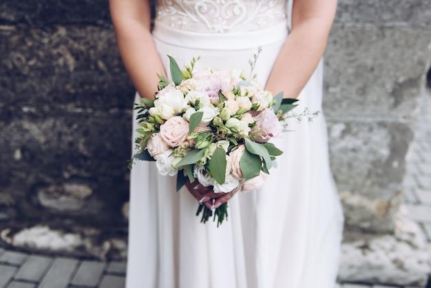 Belle jeune mariée caucasienne tenant son bouquet de mariée moderne
