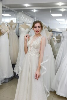 Belle jeune mariée en choisissant la robe et le voile dans le salon