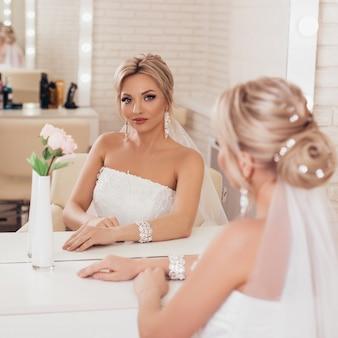 Belle jeune mariée avec coiffure de mariage blonde et maquillage dans un salon de coiffure