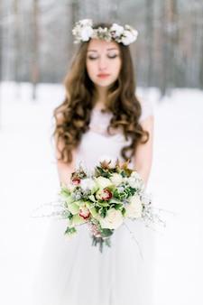 Belle jeune mariée dans la forêt enneigée d'hiver