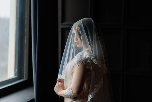 Belle jeune mariée dans une lingerie blanche. derniers préparatifs du mariage en attendant le marié.