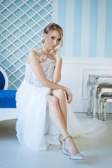 Belle jeune mariée dans une robe blanche est assise sur le canapé