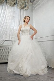 Belle jeune mariée, femme en longue robe de mariée blanche pentecôte