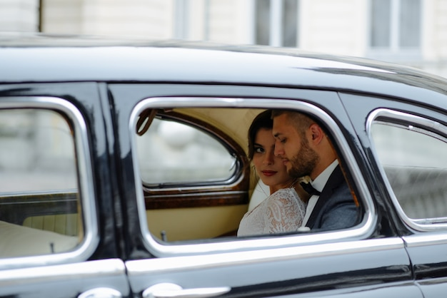 Belle jeune mariée et le marié heureux à la recherche de rétro auto