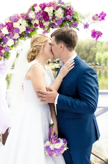 Belle jeune mariée et le marié s'embrassant sous arc à la cérémonie de mariage