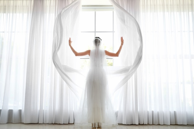 Belle jeune mariée ouvrant des rideaux sur la fenêtre avant la cérémonie de mariage à la maison, vue arrière