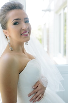 Belle jeune mariée posant contre la fenêtre dans la chambre d'hôtel