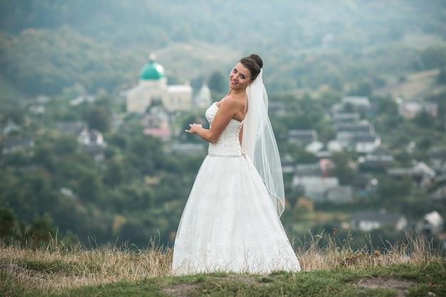 Belle jeune mariée pose pour la caméra sur le fond de la ville au loin