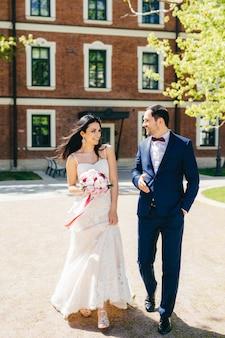 Belle jeune mariée en robe de mariée blanche, tient un bouquet, a parler avec son futur mari
