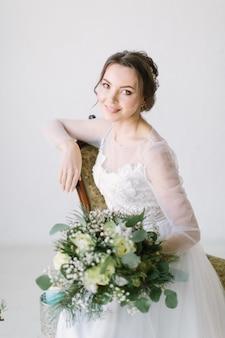 Belle jeune mariée souriante avec bouquet de fleurs assis sur une chaise