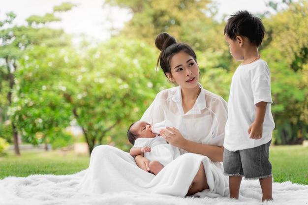 Belle jeune mère asiatique et tenant son enfant nouveau-né toucher doucement et nourrir le biberon avec amour sur l'herbe verte dans le parc