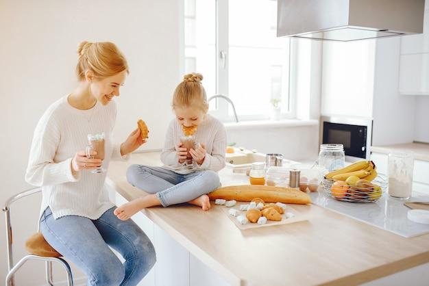 Une belle jeune mère avec des cheveux clairs en dentelle blanche et un pantalon en jeans bleu assis à la maison