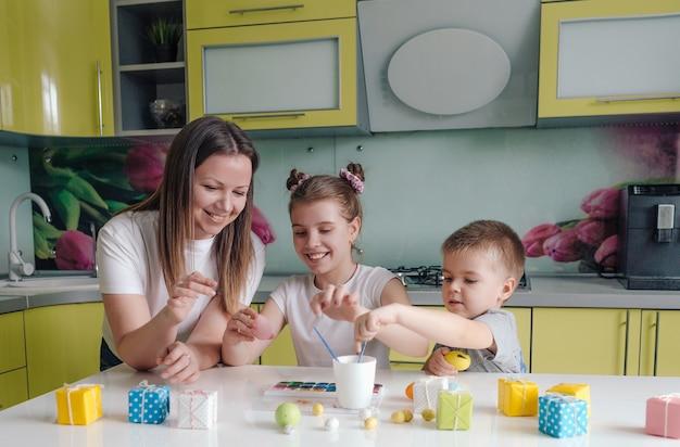 Une belle jeune mère avec deux enfants décoré des oeufs de pâques traditionnels avec de la peinture lumineuse le concept d'une famille heureuse se préparant pour les vacances de pâques