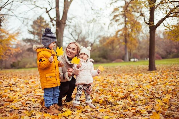 Une belle jeune mère et deux petits enfants se promènent dans le parc d'automne. maman et deux petits enfants jouent. hiver chaud. automne lumineux. confortable.