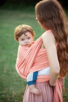 Belle jeune mère étreignant son petit fils de tout-petit contre l'herbe verte. femme heureuse avec son petit garçon sur une journée ensoleillée d'été. famille marchant sur le pré.
