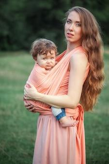 Belle jeune mère étreignant son petit fils de tout-petit contre l'herbe verte.