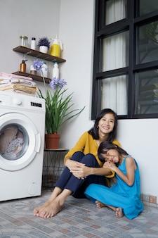 Belle jeune mère et fille asiatique en attente de la machine à laver le linge pour terminer l'essorage