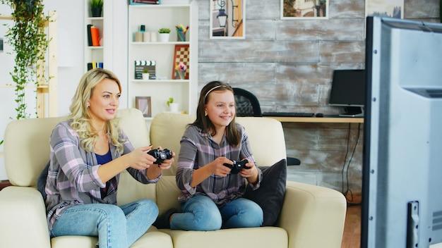 Belle jeune mère jouant à des jeux vidéo avec sa fille à l'aide d'une manette sans fil.
