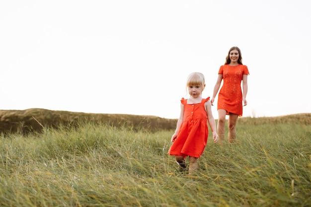 Belle jeune mère et petite fille marchant sur la nature en vacances d'été
